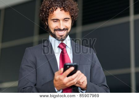 Handsome businessman typing on his mobile phone