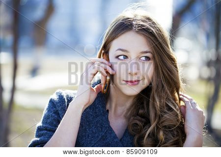 Happy beautiful girl calling by phone in spring park