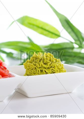 Ginger And Wasabi In White Plate With Bamboo List On Background