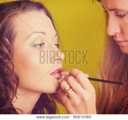 makeup artist is applying cosmetics on model face