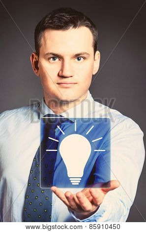 caucasian businessman is holding bulb in hands