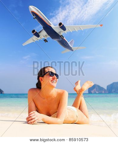 summer travel. young woman is standing on beach with aeroplane flying above
