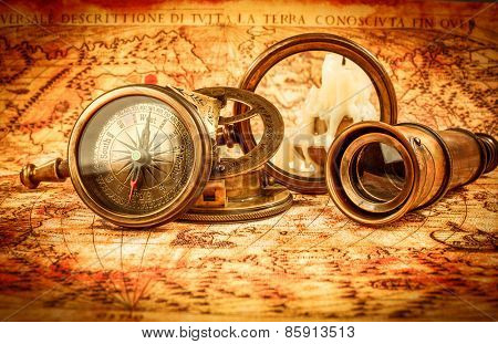 Vintage still life. Vintage magnifying glass and compass lies on an ancient world map in 1565.