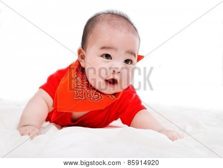 portrait of smiling baby in red dress from top on bed