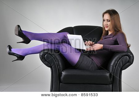 Woman Sitting In Armchair Working With Netbook