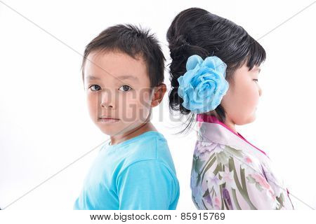 Happy boy and little girl standing back to back isolated