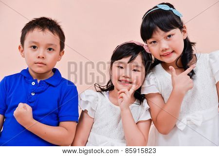 little boy and two little girl standing isolated on pink background