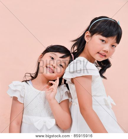 happy two asian little girls on the pink background