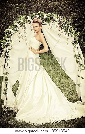 Beautiful elegant bride stands under the wedding arch. Wedding dress and accessories. Wedding decoration.