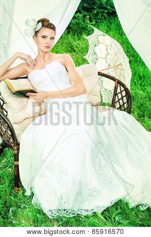 Charming elegant bride under the wedding arch. Wedding dress and accessories. Wedding decoration.