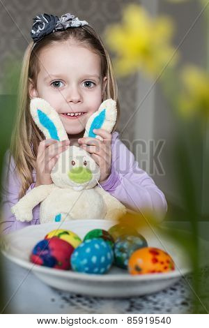 Happy little girl with toy bunny and easter eggs
