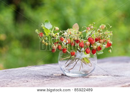 Vase With Strawberries On Wooden Table
