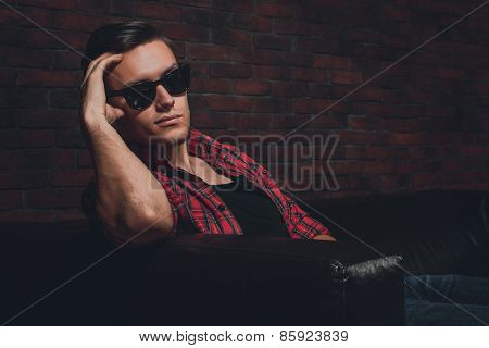 Portrait handsome young hipster man glasses casual clothes unbuttoned shirt sitting relaxing leaning
