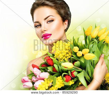 Beauty model Woman with Spring Flower bouquet. Beautiful girl with a Bouquet of colorful Tulip flowers. Happy surprised model woman smelling flowers. Mother's Day gift. Springtime