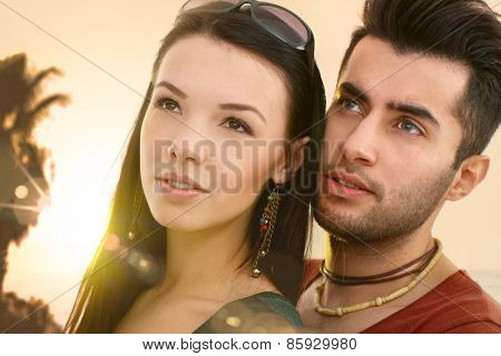 Close-up portrait of young loving couple looking away.