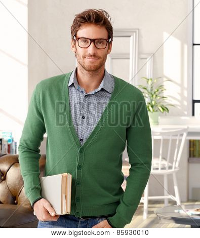Portrait of handsome man holding books, wearing glasses.