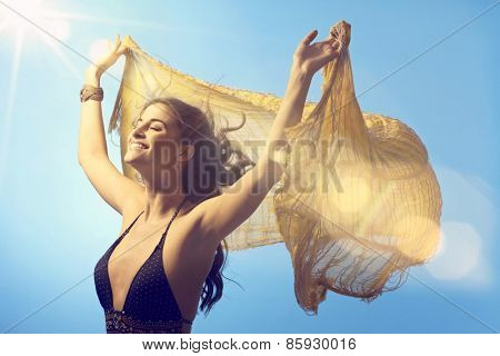 Beautiful young woman enjoying sunshine and light wind at summertime eyes closed, lifting shawl high up.