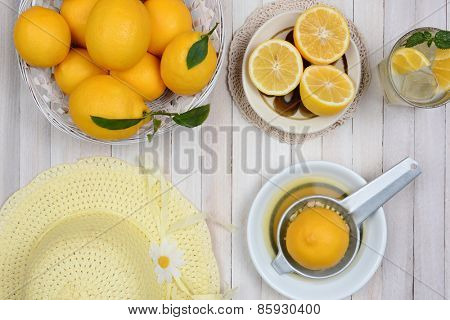 Making lemonade still life shot from a high angle on a rustic white wood kitchen table, with lemons, juicer, yellow bonnet and glass of lemonade.