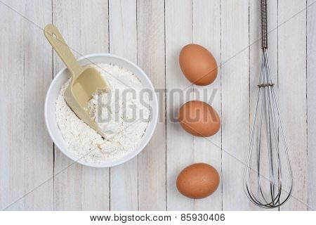 Overhead image of a bowl of flour, three brown eggs and a metal whisk on a rustic wooden kitchen table.
