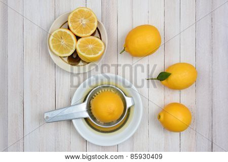 Squeezing lemons still life shot from a high angle on a rustic white wood kitchen table.