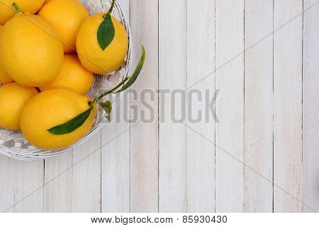 High angle shot of a basket of fresh picked lemons in the corner of the frame. Horizontal format with copy space.