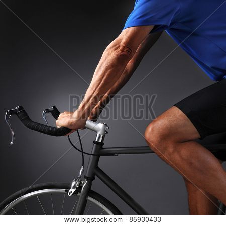 Man on a road bike on a light to dark gray background. Man is unrecognizable in closeup square format shot.