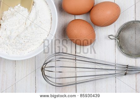 High angle closeup of three brown eggs, a bowl of flour, a whisk and strainer on a rustic white kitchen table.