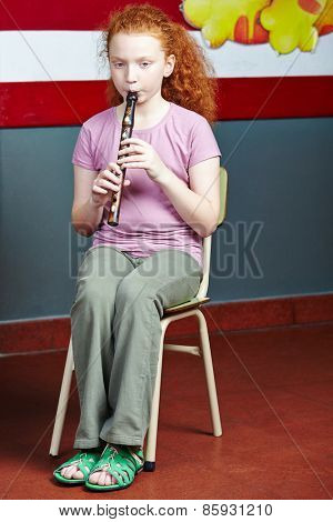Girl playing flute at music lessons in music school