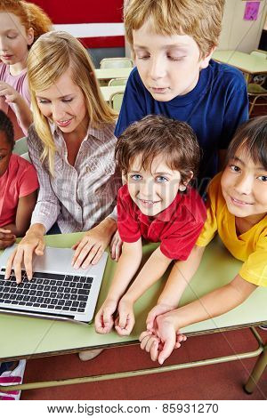 Children in elementary school class with a laptop computer
