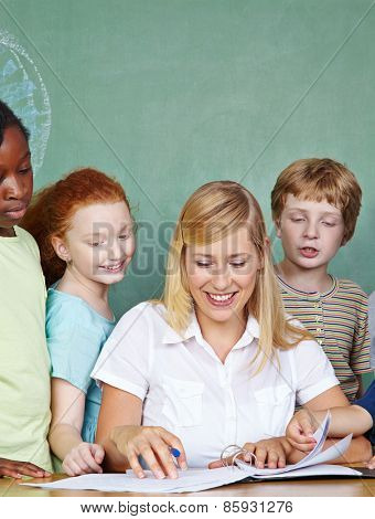 Elementary school students looking at teacher working in class at her desk