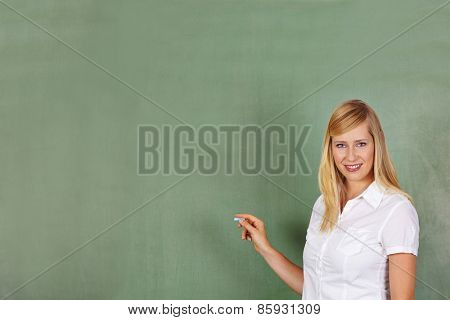 Teacher with chalk in front of empty chalkboard in school