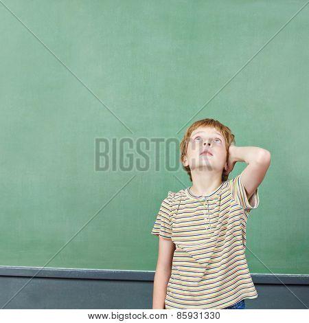 Boy standing in front of empty chalkboard thinking in elementary school