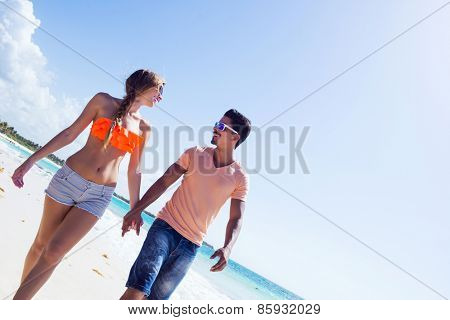Young couple having a romantic walk at the beach