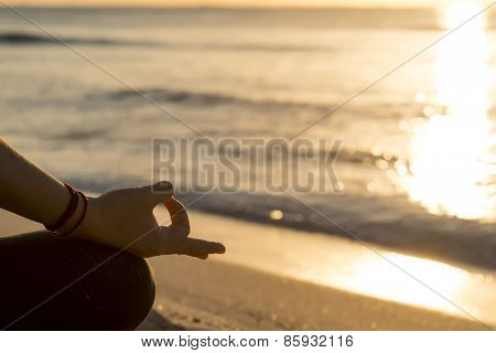 Detail of hands while meditation at the beach
