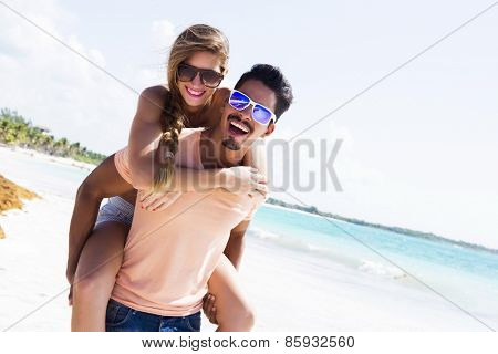 Young couple piggybacking at the beach