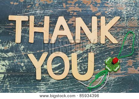 Thank you written with wooden letters and four-leaf clover on rustic wood