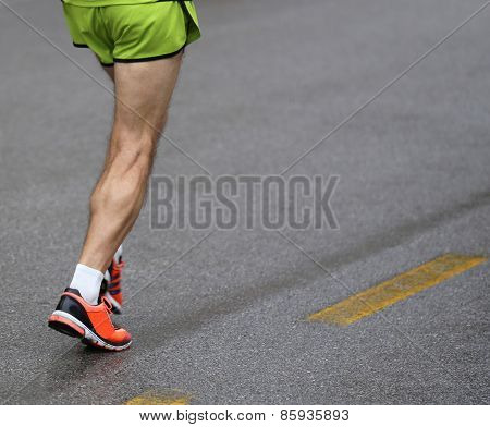 Legs Of Athlete During The Road Race And The Yellow Line