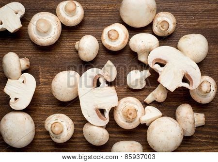 Fresh whole white button mushrooms, or agaricus, on a rustic wooden counter ready to be cleaned and