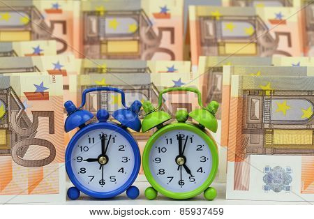 Miniature clocks showing nine and five o'clock with banknotes in the background, concept of a nine t