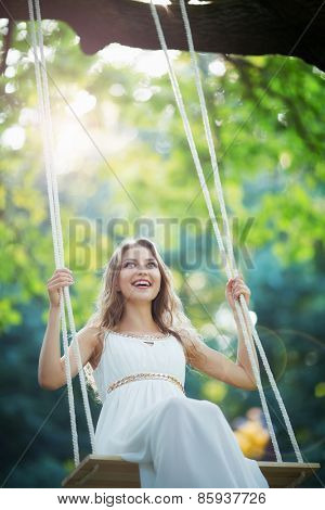 Smiling young woman on a swing