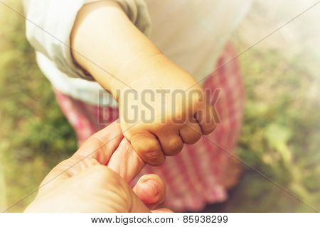 Parent holds the hand of a small child. Toned