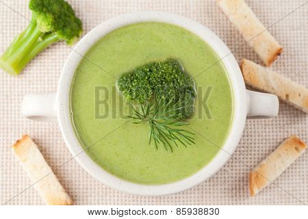 Portion of green broccoli cream soup restaraunt recipe in a white bowl