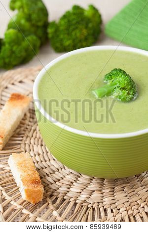 Traditional broccoli green cream soup recipe with croutons on vintage background