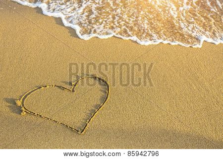 Heart drawn in sea beach sand.