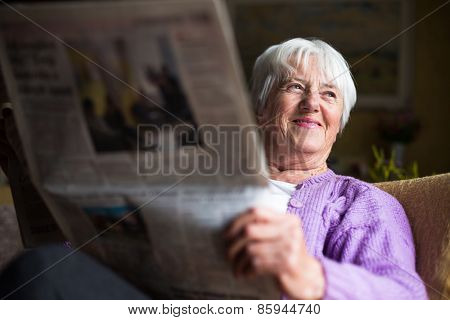Senior woman reading morning newspaper, sitting in her favorite chair in her living room, looking happy