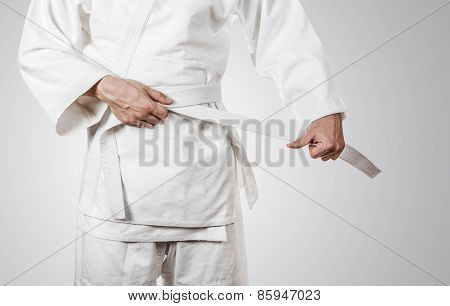 Judoka tying the white belt (obi)