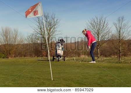 Female Golfer Chipping Golf Ball On Cup With Flag