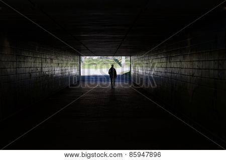 pedestrian walking through dark tunnel