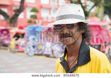 MALACCA, MALAYSIA - CIRCA JANUARY, 2015: Portrait of an unusually flamboyant man in a hat, met on the street in Malacca.