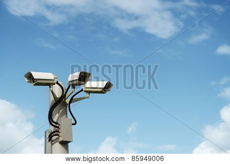 Security cctv surveillance camera in front of blue sky with copy space